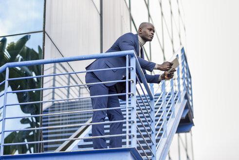 Smart businessman wearing blue suit using digital tablet outdoors - JSMF00885