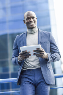 Spain, Andalusia, Malaga. Smiling black businessman wearing a blue suit in an office building environment using digital tablet. Business concept. - JSMF00888