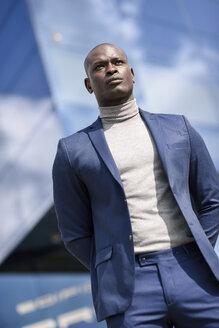 Portrait of businessman wearing blue suit and grey turtleneck pullover - JSMF00891