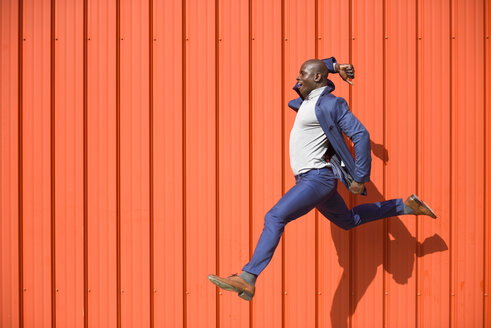 Businessman jumping in the air in front of orange wall - JSMF00900