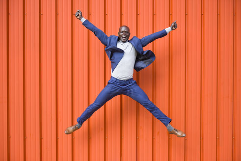 Spain, Andalusia, Malaga. Enthusiastic black businessman wearing a blue suit jumping on urban orange wall. Business concept. - JSMF00903