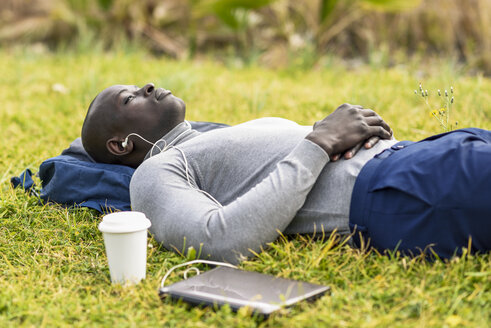 Businessman lying on a meadow listening music with earphones and laptop - JSMF00909