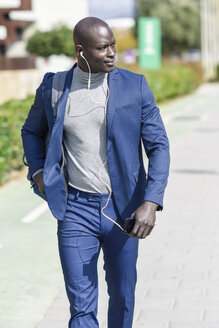 Businessman wearing blue suit listening music with earphones and smartphone - JSMF00918