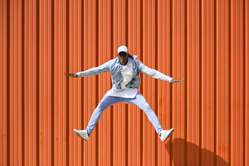 Man wearing casual denim clothes jumping in the air in front of orange wall - JSMF00927