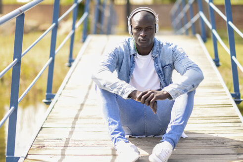Spain, Andalusia, Malaga. Young black man wearing casual denim clothes  sitting on a wooden bridge listening to the music with headphones. Lifestyle concept. - JSMF00933