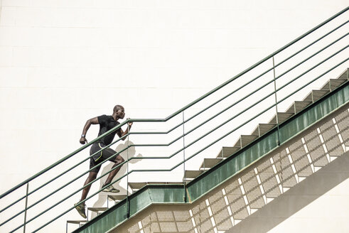 Man in black sportswear running up staircase - JSMF00939