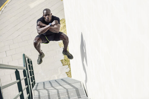 Man in black sportswear jumping in the air on staircase - JSMF00942