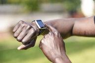 Runner checking smart watch fitness tracker, close-up - JSMF00945