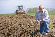 Farmer cupping soil in field with tractor and plough in background - JUIF00118