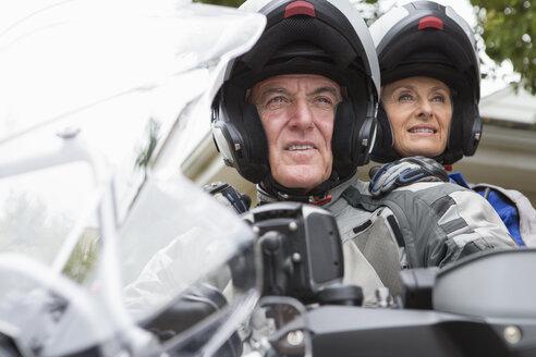Smiling senior couple wearing helmets on motorcycle - JUIF00187