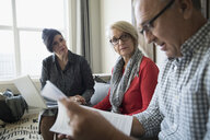 Financial advisor with laptop and paperwork meeting with senior couple in living room - HEROF30593