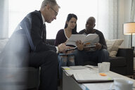 Financial advisor with calculator meeting with couple reviewing paperwork in living room - HEROF30608