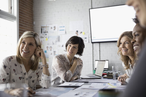 Female designers meeting and brainstorming reviewing proofs in conference room - HEROF30698