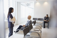 Female nurse talking to bald cancer patient in waiting room - HEROF30719