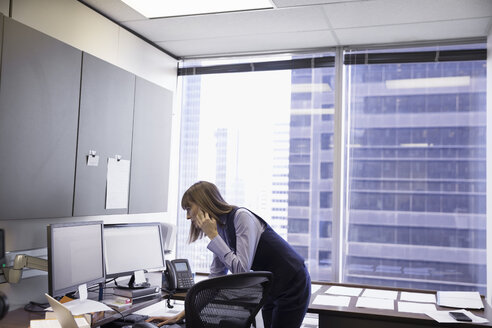 Female lawyer talking on cell phone and working at computer in office - HEROF30788