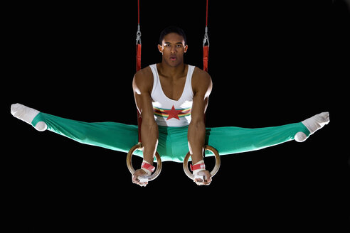 Male gymnast performing on gymnastic rings, portrait, low angle view - JUIF00219