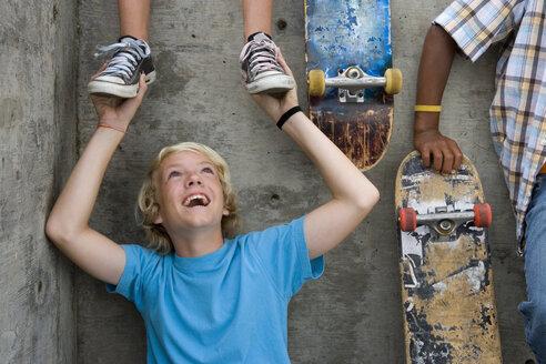 Boy (11-13) holding feet of friend on wall above, by skateboards - JUIF00228