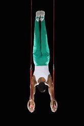 Male gymnast performing handstand on gymnastic rings, rear view - JUIF00237