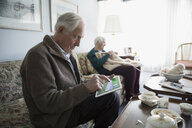 Senior couple playing solitaire on digital tablet and knitting in living room - HEROF30842