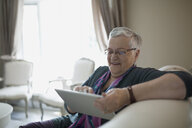 Senior woman using digital tablet on living room sofa - HEROF30872