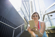 Runner with headphones and mp3 player on city steps below highrise buildings - HEROF31016