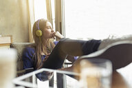 Relaxed young woman sitting on a chair wearing headphones - PNEF01322