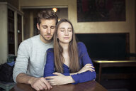 Portrait of young couple in a cafe with closed eyes - PNEF01328
