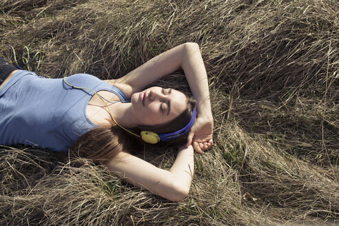 Relaxed young woman lying in meadow wearing headphones - PNEF01331