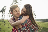 Smiling young man carrying girlfriend piggyback on meadow - PNEF01337
