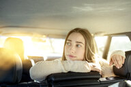Young woman sitting on back seat in car looking sideways - PNEF01340