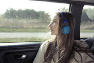 Young woman with windswept hair in a car wearing headphones - PNEF01343