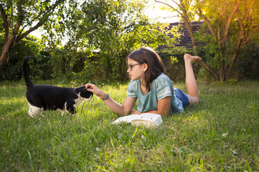 Girl with book lying on a meadow in garden tickling cat - LVF07896