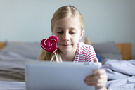 Portrait of blond girl lying on bed with lollipop using digital tablet - JPF00370