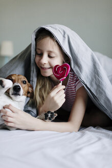 Smiling girl lying on bed with lollipop tickling her dog - JPF00373