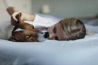 Girl lying on bed tickling her dog - JPF00376