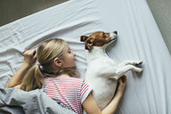 Blond girl lying on bed with her dog sleeping, top view - JPF00379