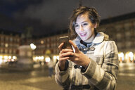 Spain, Madrid, Plaza Mayor, happy young woman using her smartphone - WPEF01389