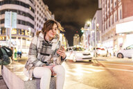 Spain, Madrid, young woman in the city at night using her smartphone and wearing earphones - WPEF01395
