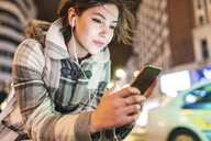 Spain, Madrid, young woman in the city at night using her smartphone and wearing earphones - WPEF01398