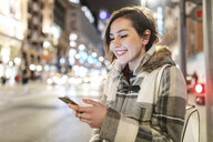Spain, Madrid, young woman in the city at night using her smartphone - WPEF01401