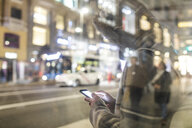 Spain, Madrid, young woman in the city at night next to Gran Via using her smartphone - WPEF01404