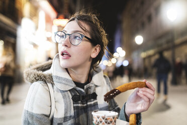 Spain, Madrid, young woman in the city at night eating typical churros with chocolate - WPEF01407