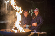Boy and girl with mugs sitting at the fire at night - LBF02497