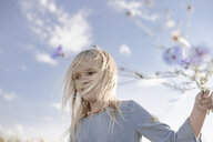Blond girl with windswept hair holding cornflowers - EYAF00039