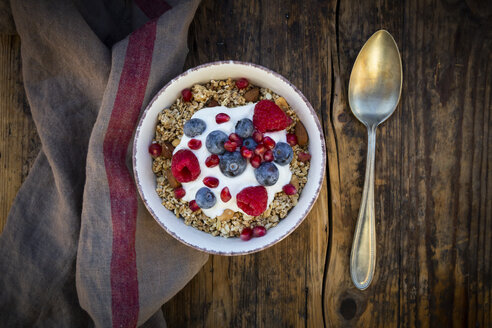 Bowl of muesli with Greek yogurt, popped quinoa, raspberries, blueberries and pomegranate seeds, from above - LVF07905