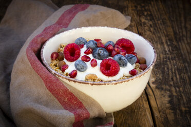 Bowl of muesli with Greek yogurt, popped quinoa, raspberries, blueberries and pomegranate seeds, from above - LVF07908