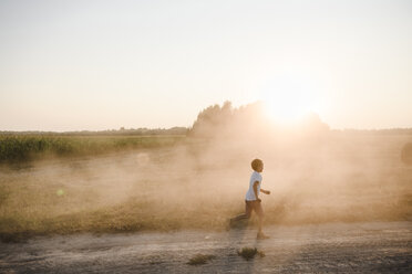 Boy running on a rural dirt track at sunset - EYAF00054