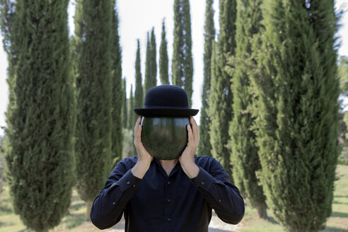 Italy, Tuscany, man surrounded by cypresses wearing a bowler hat holding a melon - PSTF00332