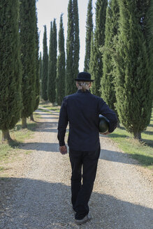 Italy, Tuscany, rear view of man surrounded by cypresses wearing a bowler hat holding a melon - PSTF00335