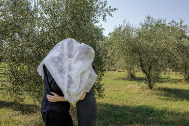 Italy, Tuscany, couple in olive grove kissing under a cloth - PSTF00344